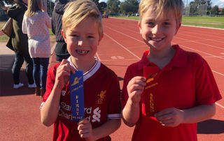 St Agnes Catholic Primary School Matraville students showcasing their ribbons in athletics