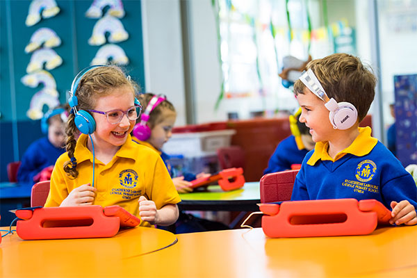 Students smiling and using tablets at St Catherine Labouré Catholic Primary School Gymea