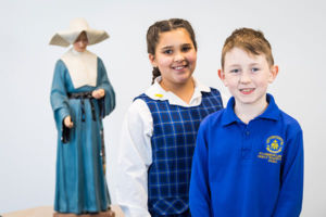 Students at St Catherine Laboure Catholic Primary School Gymea smiling in front of statue of St Agnes