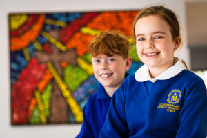 Students at St Catherine Laboure Catholic Primary School Gymea smiling in front of mural