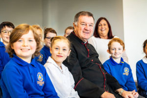 Parish Priest and Principal of St Catherine Laboure Catholic Primary School Gymea smiling with children