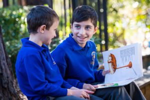 Olde student at St Catherine Labouré Catholic Primary School Gymea reading to younger student