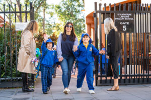 Parent walking her children into the school grounds at St Catherine Labouré Catholic Primary School Gymea
